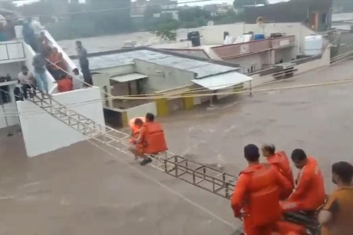 Giải cứu trẻ em vùng lũ nhờ khung sắt bắc qua các mái nhà ở Ấn Độ - Báo VietnamNet