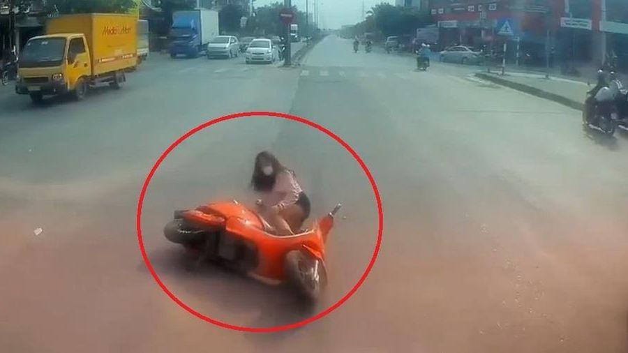 Cô gái đi xe máy vượt đèn vàng ngã trước đầu ôtô