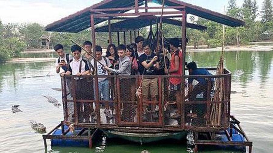 Du khách đứng trên bè tự chế vui đùa giữa bầy cá sấu khiến người xem rùng mình
