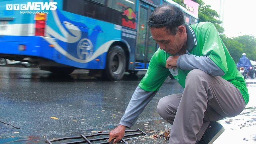 Tài xế xe ôm khơi thông cống thoát nước trên phố Hà Nội sau trận mưa lớn