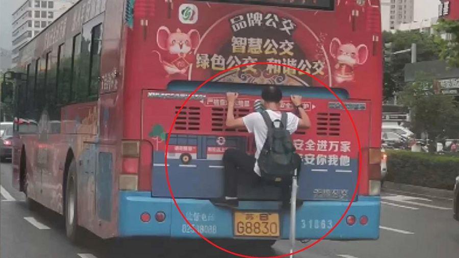 Người đàn ông bám vào đuôi xe bus để đi nhờ