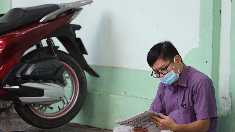 Phụ huynh trải áo mưa, ngồi đọc báo đợi con
