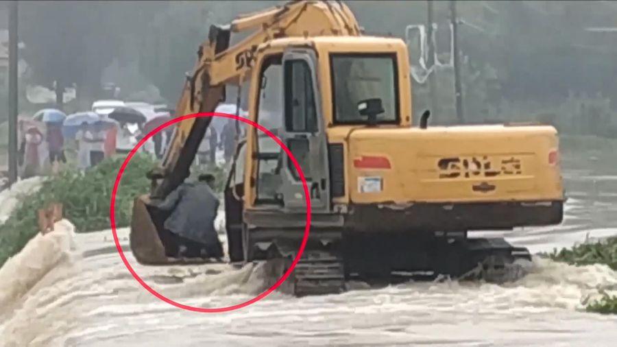 Dùng máy xúc để giải cứu người đàn ông giữa dòng nước lũ