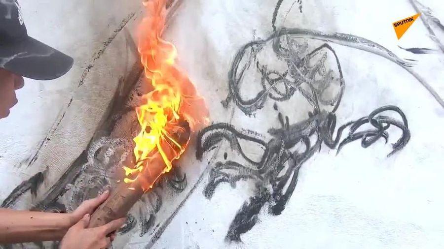 Xem họa sĩ trẻ vẽ rồng bằng que củi than đang cháy