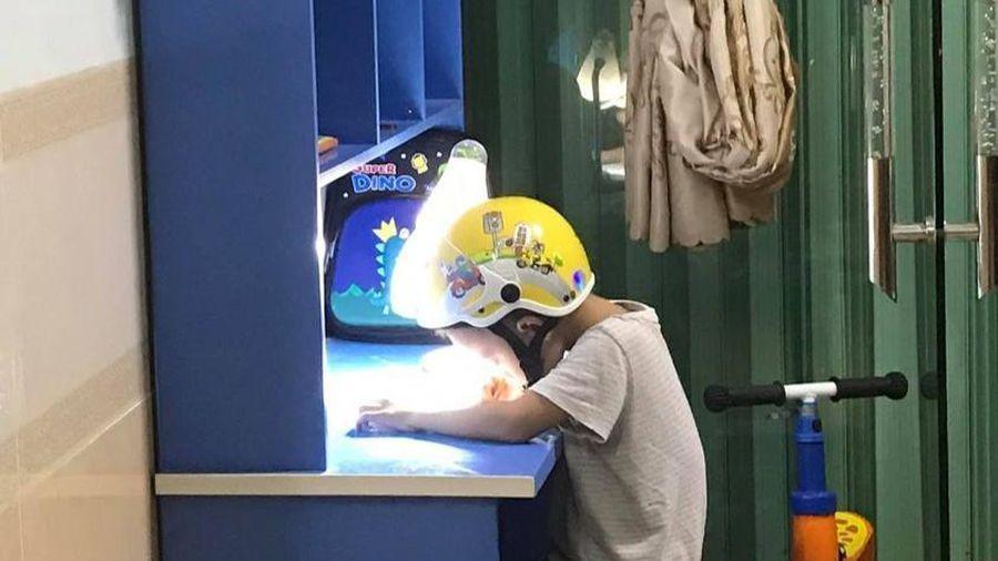 Cậu bé đội mũ bảo hiểm ngồi vào bàn học khi nghe tin chị gái sẽ hướng dẫn làm bài và sự thật khiến nhiều người thích thú