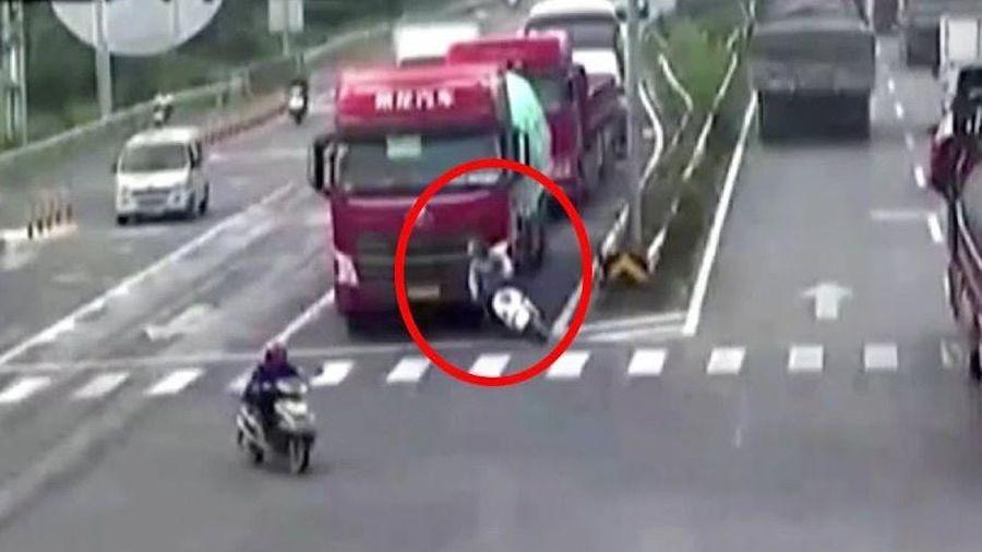Người đi xe máy sống sót khi bị xe tải cán