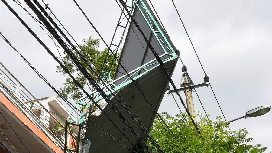 Mái tôn lơ lửng trên dây điện sau bão số 9