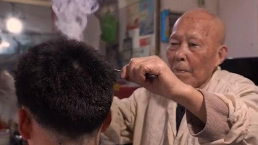 Cụ ông cắt tóc bằng thanh sắt nóng